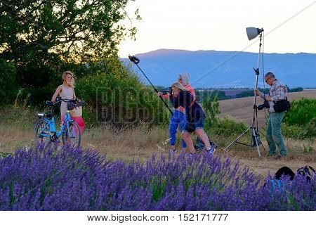 Valensole, France - July 6. 2016: Photographer and lighting assistant taking pictures of a young woman with a bicycle at sunrise at the rural road near lavender field