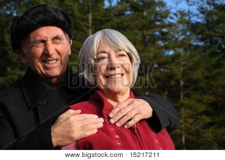 Senior couple embrace while enjoying a winter walk through a pine forest.