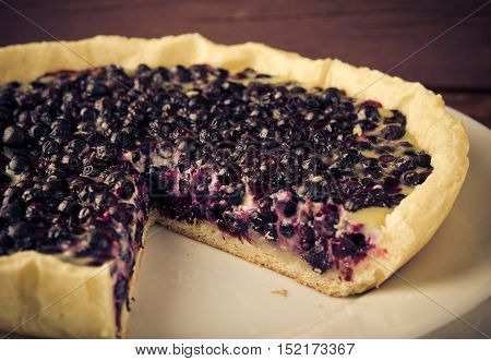 Bilberry, blueberry tart with lavender on white plate, wooden background, vintage style, toned