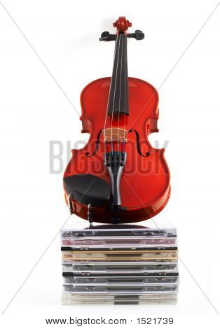 Violin Standing Upright On Stack Of Compact Discs On White Backg