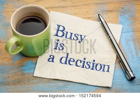 Busy is a decision - handwriting on a napkin with a cup of espresso coffee