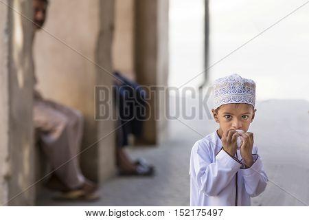 Nizwa Oman October 13th 2016: omani boy having a snack