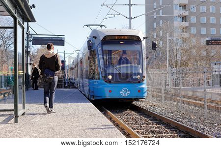 Stockholm, Sweden- March 8, 2015: An electric blue Stockholm public transport suburban tram arriving at the stop Valla torg with passangers waiting.