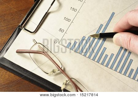 Pen in hand pointing at a bar graph on a clipboard with glasses.