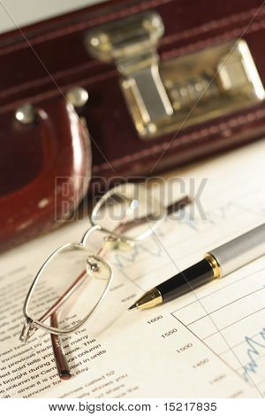 Financial charts, pen, glasses and briefcase.
