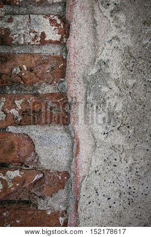 Antique wall with red old bricks and layers of plaster in Toulouse, France, closeup. Grunge background.