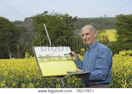 Senior male artist painting in a beautiful field full of rapeseed or canola.