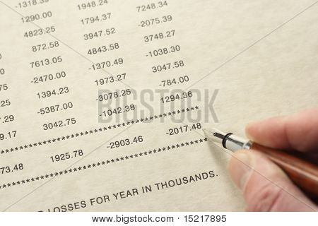 Pen pointing at disappointing year end financial figures.