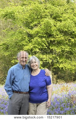 Mature couple take a walk in woodland full of beautiful springtime bluebells.