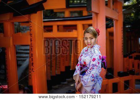 Woman Dressed In Traditional Japanese Costume Walking Under Tori Gates At The Fushimi-inari Shrine,