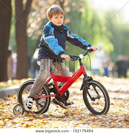 Happy boy with bicycle in the autumn park. Beauty nature scene with colorful foliage background, yellow trees and leaves at fall season. Autumn outdoor lifestyle