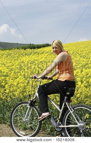Young woman enjoying a bike ride through a field full of bright yellow rapeseed.