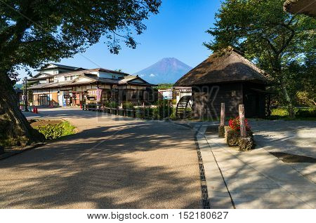 Oshino, Japan - September 2, 2016:Oshino Hakkai Fuji Five Lakes. Japan countryside street with historic thatch roof farmhouses and Mt Fuji on the background