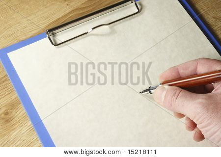 Hand with pen about to write on a piece of paper on a blue clipboard with space for text.