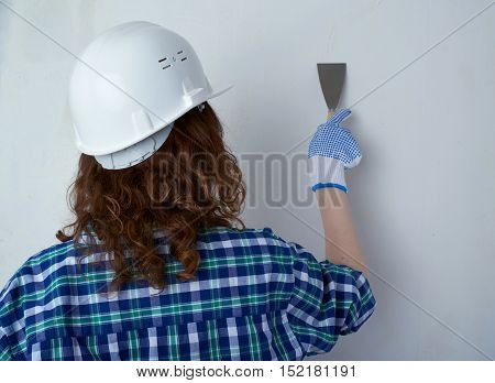 Young woman in casual clothes in front of white unpainted wall in white helmet working with putty knife, happy people and construction concept