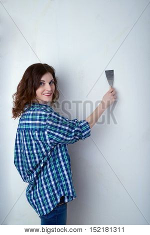 Smiling young woman in casual clothes in front of white unpainted wall working with putty knife, happy people and construction concept