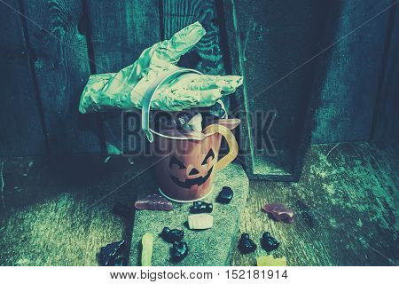 Blue halloween night background on a cute smiling pumpkin bucket being collected by a bandaged mummy hand. Taking candy from the little monsters