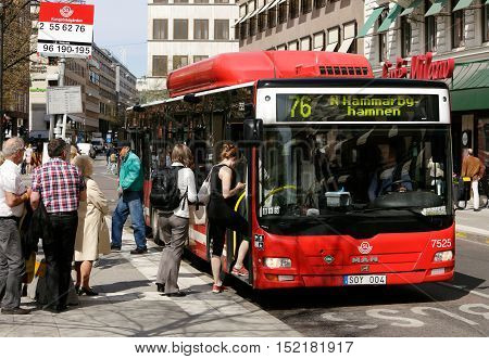 Stockholm, Sweden - May 8, 2013: Passengers boarding a public transport bus on route 76 at the stop Kungstradgarden in central Stockholm.
