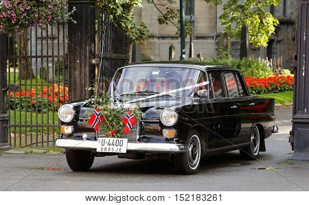 Trondheim, Norway - August 31, 2013: A newly married couple leave the cathedral in an older black Mercedes which is adorned with two Norwegian flags.