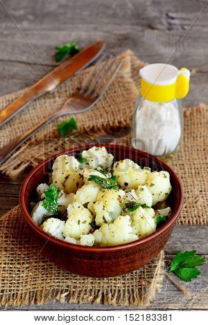 Marinated cauliflower with spices and parsley in a clay bowl, fork, knife, burlap, salt shaker on the old wooden background