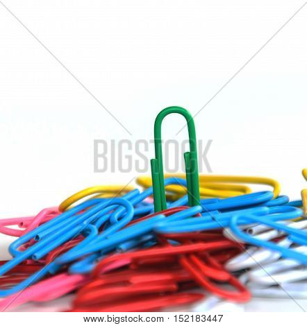 Close-up green clip on top multi-colored paper clips concept