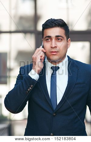 Young man talking on the mobile phone. Communication and telecommunication concept.