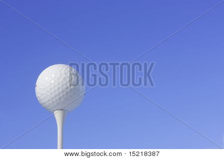 Golf ball on a white tee peg with blue sky.