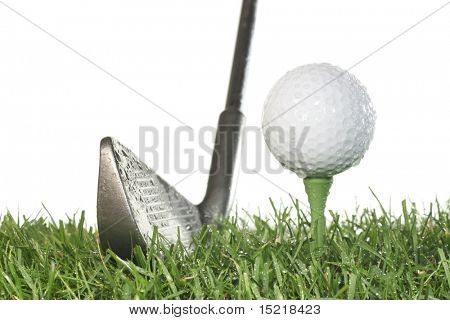 Golf club with golf ball on a tee and grass on a white background in damp conditions.