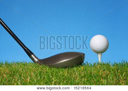 Preparing to drive a golf ball off a tee with grass and a blue background.