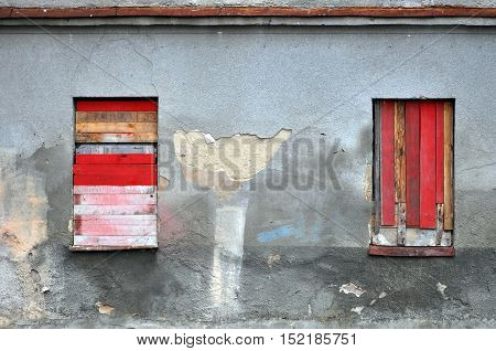Gray wall of abandoned building with peeling plaster and the two boarded-up windows.