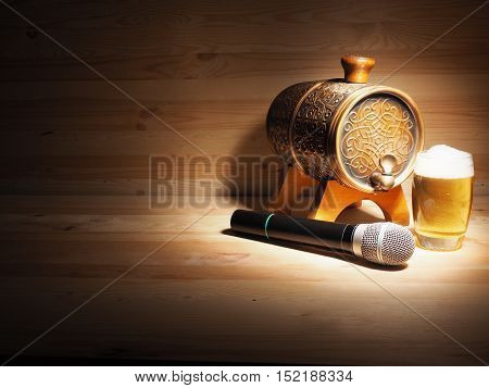 Barrel and glass of beer microphone on wooden background. concept karaoke.