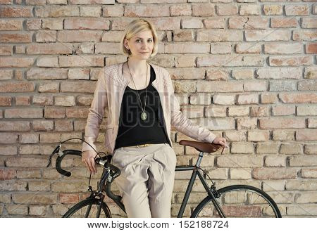 Young blonde woman standing against bicycle front of brick wall.