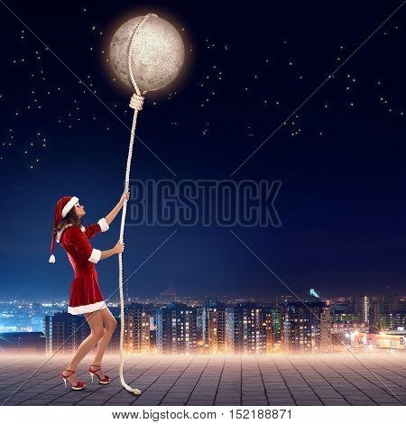 Elegant Santa woman pulling moon planet on rope