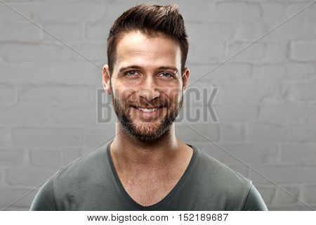 Portrait of happy young handsome man against white brickwall.