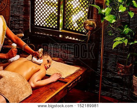 Woman having Ayurveda massage with herbal ball. Green plants outside.