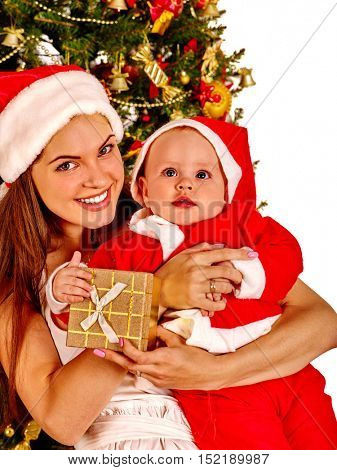 Mom wearing Santa hat holding baby with gift box under Christmas tree on isolated. Children's holiday. Family celebration.