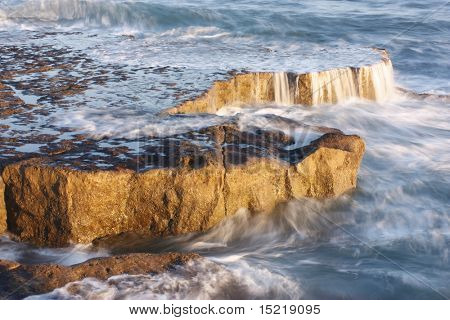 Long exposure of breaking waves over rocks at sunset.