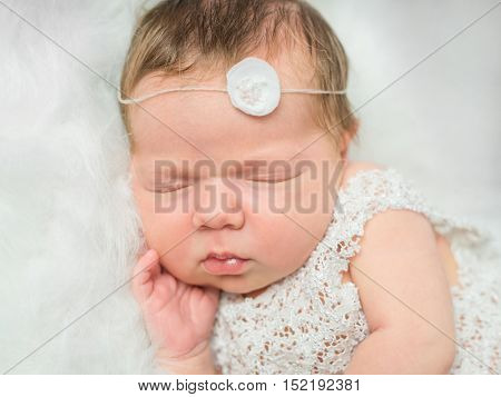 beautiful newborn girl sleeping on white fluffy plaid with little toy