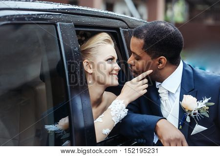 Happy newlyweds of beautiful bride woman in car and african American groom man share love outdoors on wedding day
