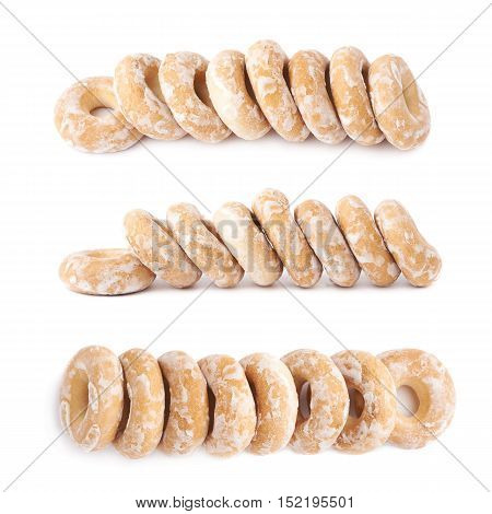 Pile of sushki round small dried cakes with hole with sugar powder isolated over the white background