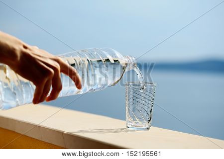 Female hand pours pure drinking water from plastic bottle into glass outdoors on summer day on blue sea