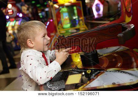 Boy shooting a gun in an amusement park
