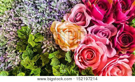 Decorative background artificial roses and flowers on a wall.