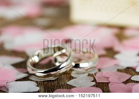Wedding Rings On A Wooden Background With Confetti