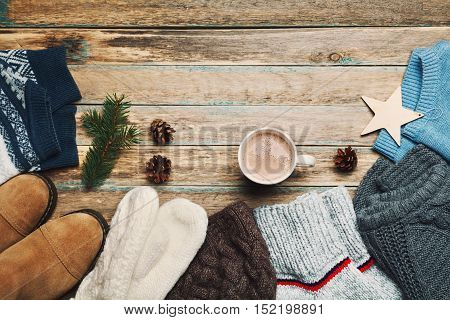 Autumn or winter clothes, sweater, shoes, mittens, fir tree and hot cocoa on wooden vintage background from above. Flat lay.