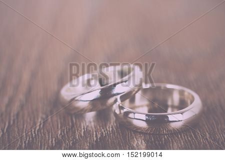 Pair Of Wedding Rings On A Wooden Background Vintage Retro Filter.
