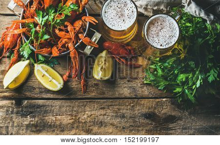 Two mugs of wheat beer and boiled crayfish in pan served with with lemon and parsley over rustic wooden background, top view, copy space, horizontal composition