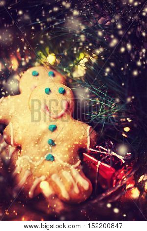 Christmas decorations - gingerbread man cookie over dark festive background.