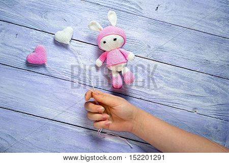 girls hand holding balloons crocheted giving the hearts to knit bunny as a birthday gift. wooden background with copy space for your congratulatory text