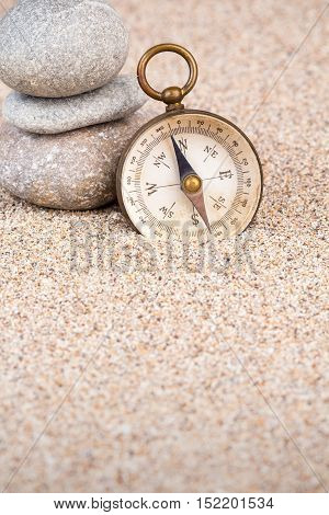 Vintage compass with three pebble stones on sand portrait view
